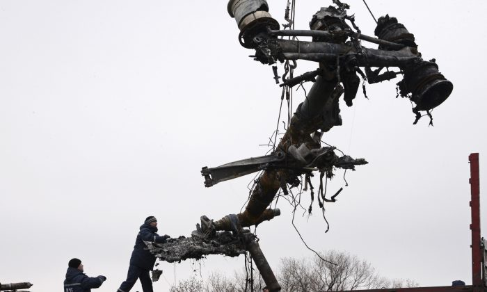 Recovery workers in rebel-controlled eastern Ukraine load debris from the crash site of Malaysia Airlines Flight 17, in Hrabove, Ukraine, Sunday, Nov. 16, 2014, four months after the plane was brought down.  (AP Photo/Mstyslav Chernov)