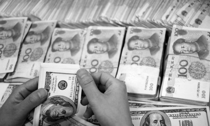 U.S. dollar notes are counted next to stacks of Chinese 100 yuan (RMB) bank notes at a bank in Huaibei, in eastern China's Anhui province, on Sept. 23, 2014. (STR/AFP/Getty Images)