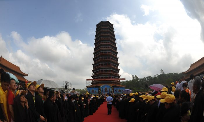 Monks and citizens conduct the ceremony of blessings by seeing first light of a Buddhist pagoda at Jinshan Temple on Oct. 22, 2014 in Chengmai, Hainan province of China. The practice of religion is off limits for Chinese Communist Party members, according to an opinion piece in Global Times by a high-ranking Party member. (ChinaFotoPress/ChinaFotoPress via Getty Images)