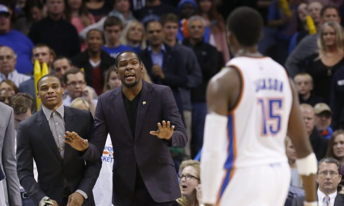 Oklahoma City Thunder's Kevin Durant, center, gestures to teammate Reggie Jackson (15) during a timeout in the fourth quarter of an NBA basketball game against the Detroit Pistons in Oklahoma City, Friday, Nov. 14, 2014. Detroit won 96-89 in overtime. (AP Photo/Sue Ogrocki)
