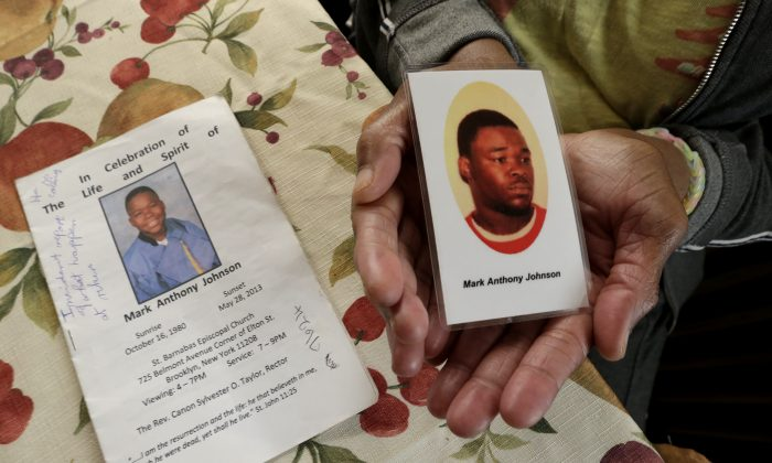 June Broer displays a funeral program and a prayer card featuring images of her only son, Mark Johnson, in Paterson, N.J., on Oct. 18, 2014. For days, Johnson demanded medical care from jail guards at Rikers Island as he continued to have bloody stools before he died of a bacterial infection. (AP Photo/Julio Cortez)