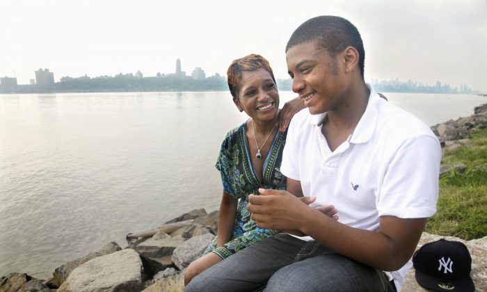 Rachel Noerdlinger and her son Khari, 14, sit at the edge of the Hudson River near their home in Edgewater, N.J., across from Harlem, N.Y., on Tuesday, June 28, 2011. Noerdlinger previously lived in Harlem for 16 years before moving to Edgewater.  (AP Photo/Bebeto Matthews)
