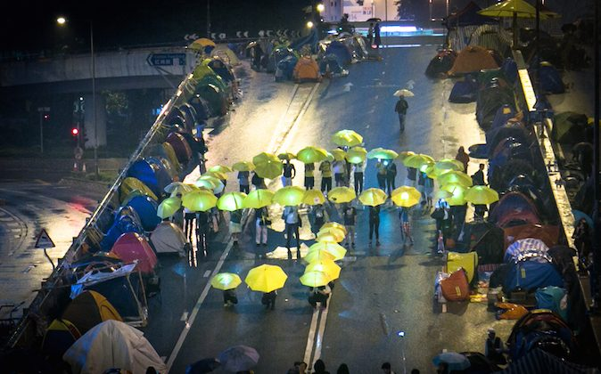 Pro-democracy protesters hold yellow umbrellas as they stand in a pattern forming a large umbrella in the Central District in Hong Kong on Nov. 8, 2014. (Benjamin Chasteen/Epoch Times)