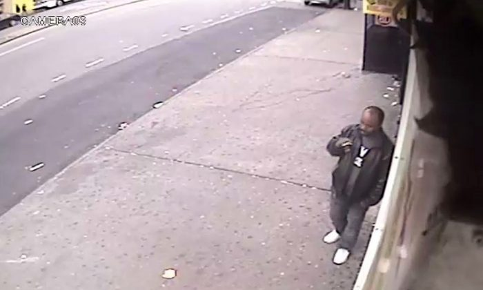 In this surveillance video a man smokes a cigarette outside a convenience store in the Bronx borough of New York on Sunday, Nov. 16, 2014. The NYPD says the man is suspected of shoving a stranger off a subway platform Sunday in front of an oncoming subway train. (AP Photo/New York Police Department)