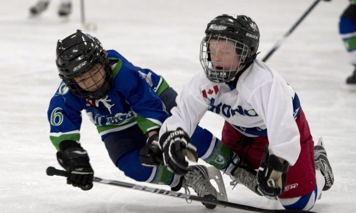 Two kids playing hockey fall to the ice in a novice-level game. Children playing hockey need to have greater respect for their fellow players as a preventative measure against concussions. (The Canadian Press/Doug Ives)