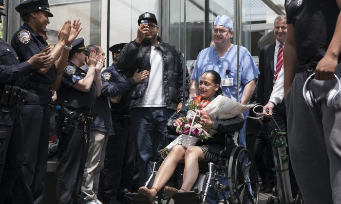 New York City police officer Rosa Rodriguez leaves the Weill Cornell Medical Center in Manhattan, New York on May 19, 2014, after recovering from a critical injury she suffered while responding to an apartment building fire. The city's police union is urging the City Council to support a state bill that would increase pensions for officers permanently injured while on duty. (Samira Bouaou/Epoch Times)