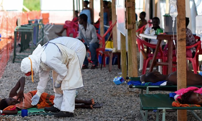 A nurse wearing personal protective equipment (PPE) checks on a patient at the Kenama ebola treatment center run by the Red Cross Society on November 15, 2014. Ebola-hit Sierra Leone faces social and economic disaster as gains made since the country's ruinous civil war are wiped out by the epidemic, according to a major study released on November 13. (AFP/Getty Images)