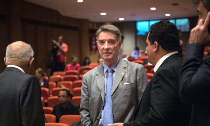 Brazilian businessman Eike Batista (C), once Brazil's richest man, talks with his lawyers during a break on the first day of his trial for alleged insider trading in Rio de Janeiro, Brazil, on November 18, 2014. (YASUYOSHI CHIBA/AFP/Getty Images)