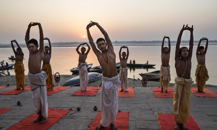 Young Indian perform yoga on a ghat on the Ganges River, at sunrise on April 23, 2014 in Varanasi, India.  (Kevin Frayer/Getty Images)