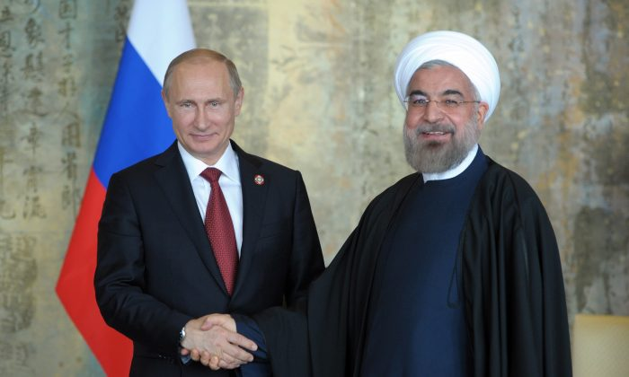 Russia's President Vladimir Putin (L) shakes with his Iran's counterpart Hassan Rouhani during their bilateral meeting in Shanghai on May 21, 2014. (Alexey Druzhinin/AFP/Getty Images)