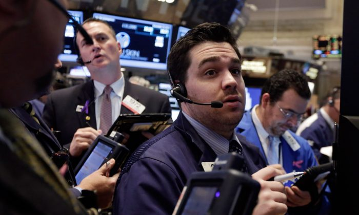Traders gather at a post on the floor of the New York Stock Exchange, Tuesday, Nov. 18, 2014. Major US stocks opened higher on Tuesday, a day after the Standard & Poor's 500 index set its second record-high close in two days. (AP Photo/Richard Drew)