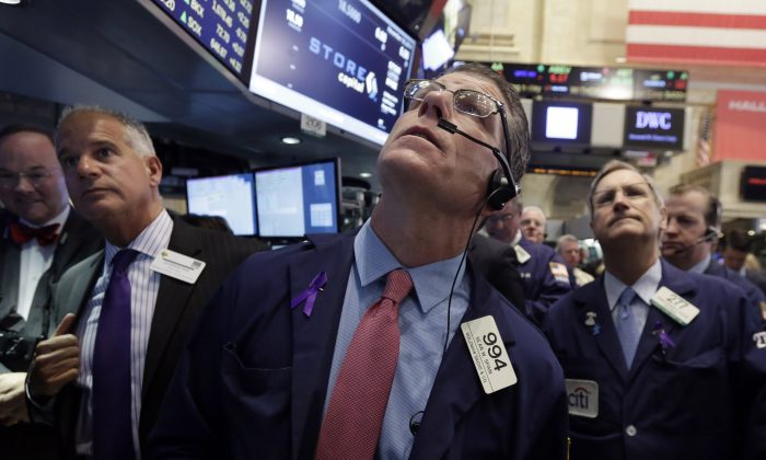 Trader Sean Spain, center, works on the floor of the New York Stock Exchange, Tuesday, Nov. 18, 2014. Stocks moved higher in late afternoon trading Tuesday, on track to deliver a record-high close for the Dow Jones industrial average and Standard & Poor's 500 index. (AP Photo/Richard Drew)
