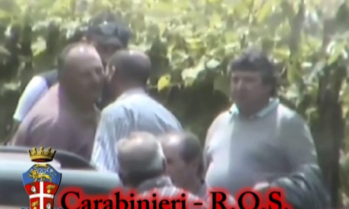 "In this photo taken from a video provided by the Italian Carabinieri (paramilitary police), people identified by police as Italian cryme sindicate 'ndrangheta' members kiss each other. Police in northern Italy say for the first time they have video of a secret, ritual swearing-in ceremony for the 'ndrangheta', a powerful Italian crime syndicate. Their investigation also led to 40 arrests in a crackdown of extortion by mobsters preying on businesses in Lombardy and across the border in Switzerland. Milan Prosecutor Ilda Boccassini told reporters Tuesday the video of the ritual ceremony for recruits shows how the strength of the 'ndrangheta' is the force of tradition."" (AP Photo/Carabinieri)"