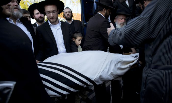 Orthodox Jews carry the body of Mosheh Twersky during his funeral in Jerusalem, Tuesday, Nov. 18, 2014. Two Palestinian cousins armed with meat cleavers and a gun stormed a Jerusalem synagogue during morning prayers Tuesday, killing Twersky and three other people in the city's bloodiest attack in years. Police killed the attackers in a shootout. (AP Photo/Oded Balilty)