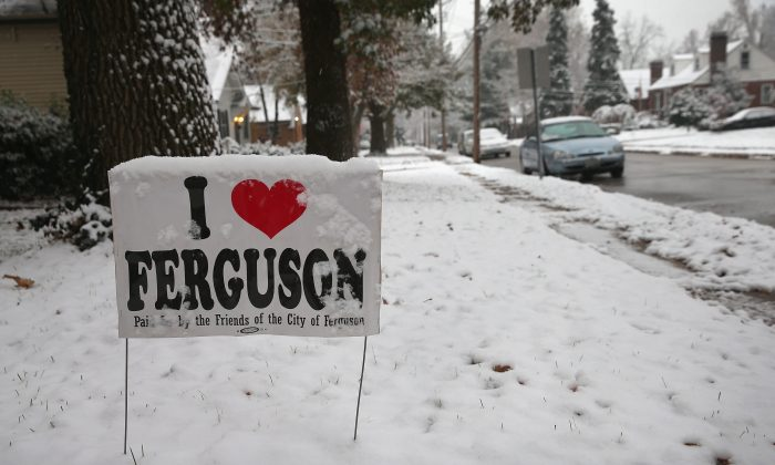 Snow covers a yard sign placed outside a home near the police station on November 16, 2014 in Ferguson, Missouri. The signs began appearing around Ferguson after riots rocked the town following the shooting death of 18-year-old Michael Brown by Darren Wilson, a Ferguson police officer, on August 9. (Scott Olson/Getty Images)