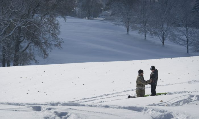 A father and son sled in a file photo. (AP Photo/The Evansville Courier & Press, Denny Simmons)