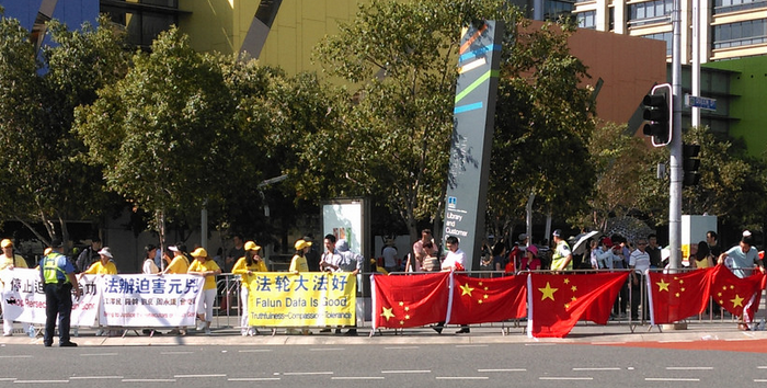 Chinese students leave their flags [one upside down] on the fence while they sit in the shade some distance away, on Saturday Nov. 15, 2014. After a large number of students tried to cover the Falun Gong banners and practitioners with the red flags the police instructed the Chinese students and their flags to move to the opposite side of the road. (Courtesy of Bethany Liu)