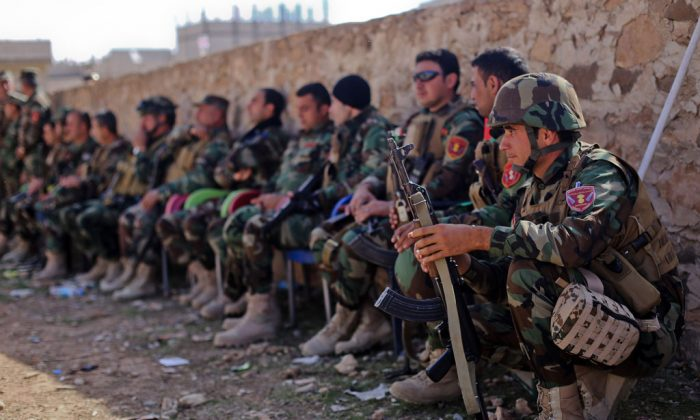 Kurdish Peshmerga fighters rest during fighting against Islamic State (IS) group on Nov. 8, 2014, in the Syrian besieged border town of Ain al-Arab (known as Kobani by the Kurds). US-led air strikes hit jihadist positions in the north and east of Syria, including an oil field, the Syrian Observatory for Human Rights said. (Ahmed Deeb/AFP/Getty Images)