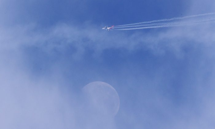 A Qantas airplane flies over the moon during a Collingwood Magpies AFL Fitness Camp on Nov. 14, 2014, in Falls Creek, Australia. (Michael Dodge/Getty Images)