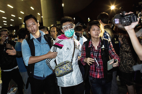Police detain a man wearing protective as pro-democracy protesters faced-off with police outside the central government offices on November 19, 2014 in Hong Kong. (Lam Yik Fei/Getty Images