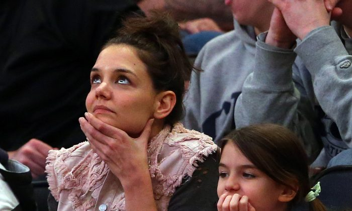 Actress Katie Holmes and her daughter Suri Cruise attend the East Regional Final of the 2014 NCAA Men's Basketball Tournament between the Connecticut Huskies and the Michigan State Spartans at Madison Square Garden on March 30, 2014 in New York City. (Photo by Elsa/Getty Images)