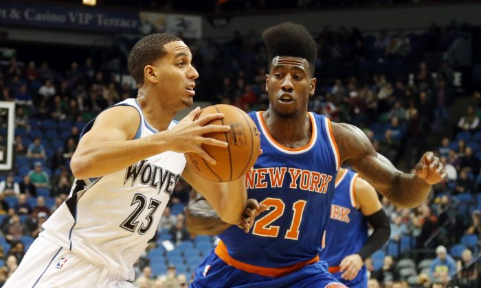 Minnesota Timberwolves' Kevin Martin, left, drives around New York Knick' Iman Shumpert in the first quarter of an NBA basketball game, Wednesday, Nov. 19, 2014, in Minneapolis. (AP Photo/Jim Mone)