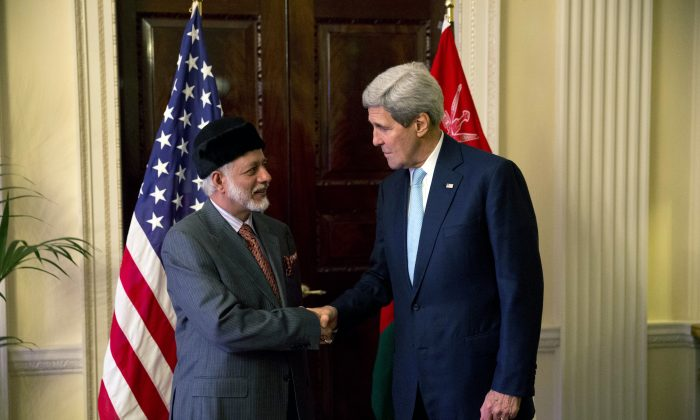 U.S. Secretary of State John Kerry, right, and Oman Foreign Minister Yusuf Bin Alawi bin Abdullah perform a posed handshake for photographers at the start of their meeting at the official residence of the U.S. ambassador to Britain, Winfield House, in London, Tuesday, Nov. 18, 2014.  (AP Photo/Matt Dunham)