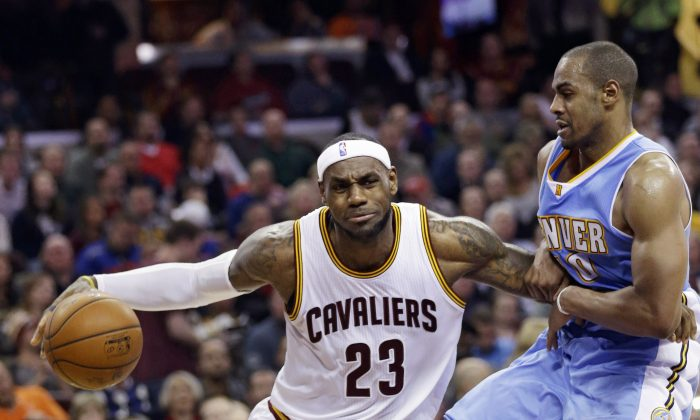 Cleveland Cavaliers' LeBron James (23) drives past Denver Nuggets' Arron Afflalo (10) during the second quarter of an NBA basketball game Monday, Nov. 17, 2014, in Cleveland. (AP Photo/Tony Dejak)
