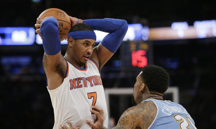 New York Knicks forward Carmelo Anthony (7) looks to pass with Denver Nuggets forward Wilson Chandler (21) defending in the second half of an NBA basketball game at Madison Square Garden in New York, Sunday, Nov. 16, 2014.  Anthony had 28 points as the Knicks defeated the Nuggets 109-93. (AP Photo/Kathy Willens)