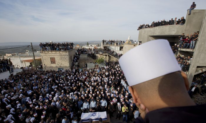A Druze man watches as others surround the flag draped coffin during the funeral of Druze Israeli police officer Zidan Sif in the Druze village of Yanuh-Jat, northern Israel, Wednesday, Nov. 19, 2014. Sif, 30, died of his wounds on Tuesday after Two Palestinian cousins armed with meat cleavers and a gun stormed a Jerusalem synagogue during morning prayers Tuesday, killing four people in the city's bloodiest attack in years. Police killed the attackers in a shootout. (AP Photo/Ariel Schalit)