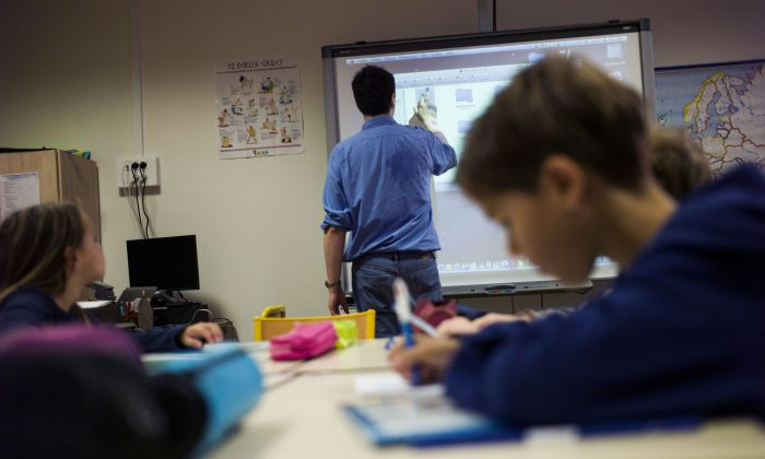 A teacher uses a touchpad board during his lesson at an elementary school on September 9, 2014 in Paris. (Fred Dufour/AFP/Getty Images)