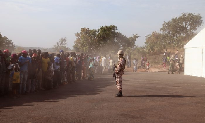 A Mali soldier (C) controls a crowd of people during a visit by their president, Ibrahim Boubacar Keita, at the border village of Kouremale, Mali, between Mali and Guinea, on Nov. 17, 2014. On Mali's dusty border with Ebola-stricken Guinea, travelers have a new stop: Inside a white tent, masked medical workers zap incomers with infrared thermometer guns and instruct them to wash their hands in chlorinated water. (AP Photo/Baba Ahmed)