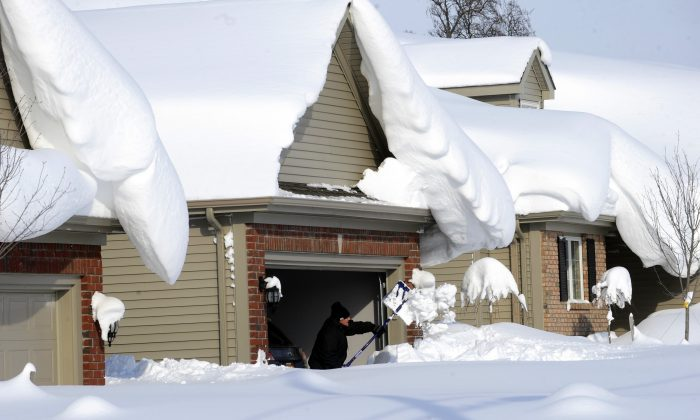 Snowdrifts create a beautiful setting as a man tries to dig out his driveway on Bowen Road in Lancaster, N.Y., on Wednesday, Nov. 19, 2014. (AP photo/Gary Wiepert)