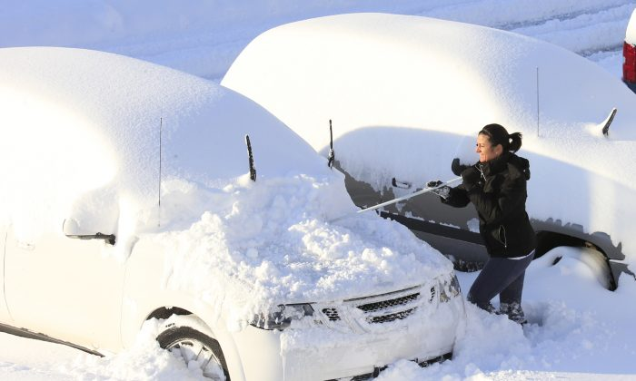 Christine Bloom works to clear snow off her vehicle to try and make it to work in Hamburg, N.Y.,  on Wednesday, Nov. 19, 2014.   (AP Photo/The Buffalo News, Harry Scull Jr.)