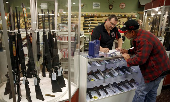 In this Saturday, Nov. 15, 2014 photo, Steven King, left, fills out paperwork before selling a handgun to first-time gun owner Dave Benne at Metro Shooting Supplies, in Bridgeton, Mo. King says he's sold two to three times more weapons in recent weeks than normal as a grand jury decides whether to indict Ferguson police Officer Darren Wilson in the shooting death of Michael Brown. (AP Photo/Jeff Roberson)