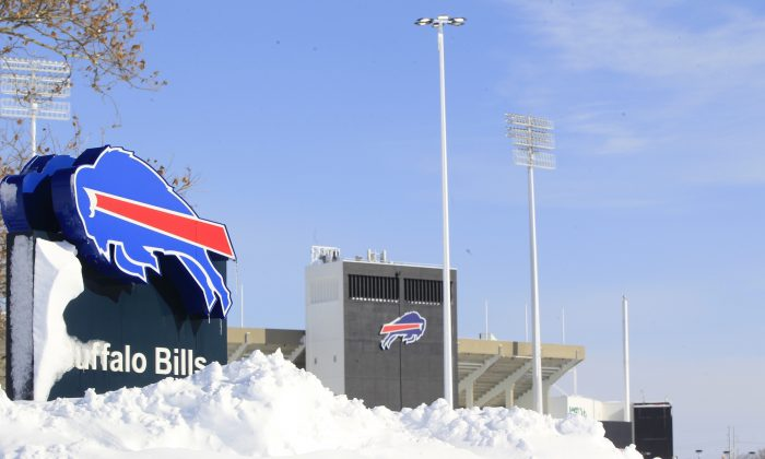 Snow covers  a sign at Ralph Wilson Stadium,  home of the Buffalo Bills in Orchard Park, N.Y. on Wednesday, Nov. 19, 2014.  A ferocious lake-effect storm left the Buffalo area buried under 6 feet of snow Wednesday, trapping people on highways and in homes, and another storm expected to drop 2 to 3 feet more was on its way. (AP Photo/The Buffalo News, Harry Scull Jr.)  TV OUT; MAGS OUT; MANDATORY CREDIT; BATAVIA DAILY NEWS OUT; DUNKIRK OBSERVER OUT; JAMESTOWN POST-JOURNAL OUT; LOCKPORT UNION-SUN JOURNAL OUT; NIAGARA GAZETTE OUT; OLEAN TIMES-HERALD OUT; SALAMANCA PRESS OUT; TONAWANDA NEWS OUT