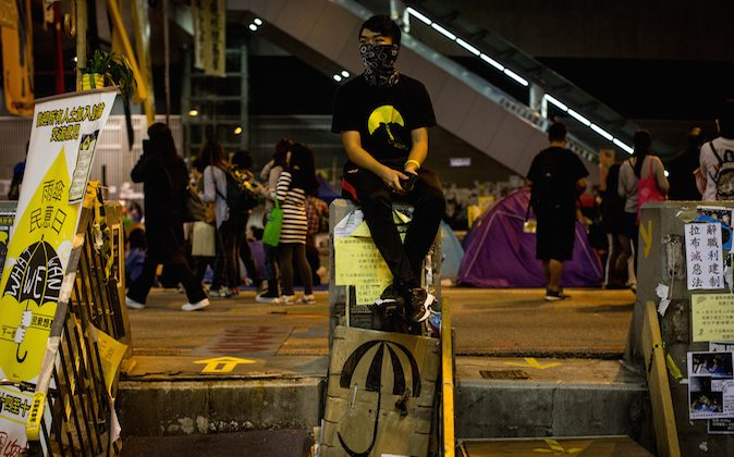 A pro-democracy activists sits between a set of makeshift stairs on the street outside Hong Kong's Government complex on November 16, 2014 in Hong Kong. (Chris McGrath/Getty Images)