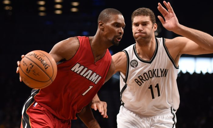 Miami Heat center Chris Bosh drives on Brooklyn Nets center Brook Lopez during their NBA game November 17, 2014 at the Barclay Center in New York. (AFP/Getty Images)