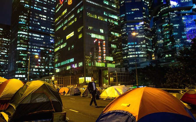 A business man walks through rows of tents setup by pro-democracy activists on the road outside Hong Kong's Government complex on November 20, 2014 in Hong Kong. (Chris McGrath/Getty Images)