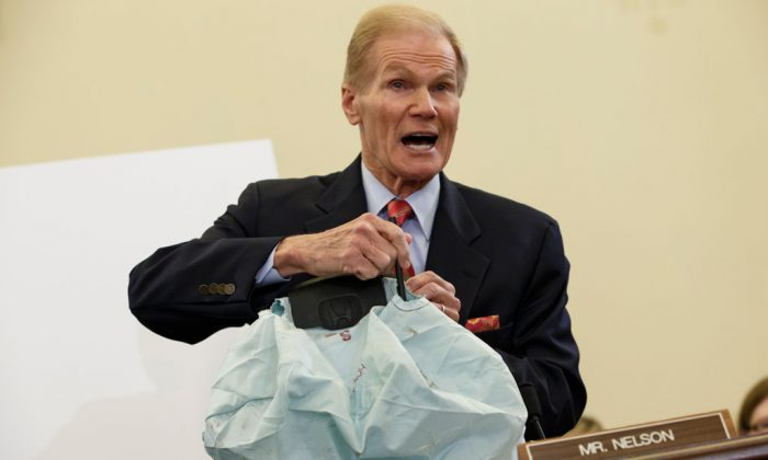 Senate Commerce Committee member Sen. Bill Nelson (D-Fla.) displays the parts and function of a defective airbag made by Japan's Takata Corp. that has been linked to multiple deaths and injuries in cars driven in the United States, during the committee's hearing on Capitol Hill in Washington, D.C., on Nov. 20, 2014. (AP Photo/J. Scott Applewhite)