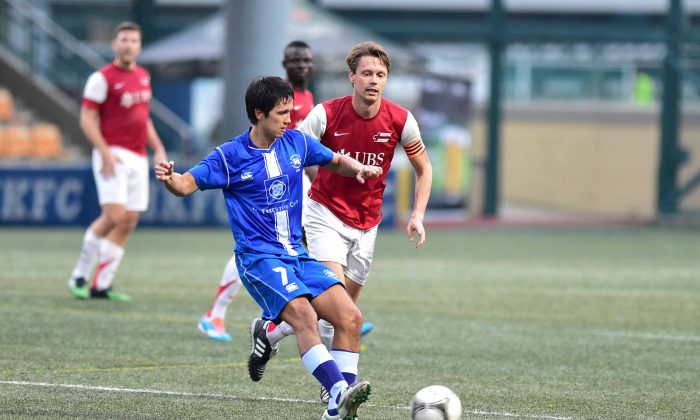 lbion's Tim Phillips (blue kit) tries to progress against Swiss XI in their Yau Yee League First Division match at Sports Road on Sunday Nov. 16, 2014. A late score by Swiss XI secures a 1-0 win. (Bill Cox/Epoch Times)