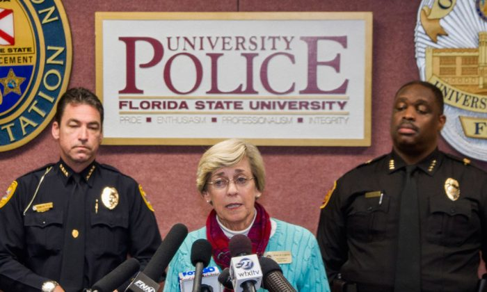 Mary Coburn (C), vice president of student affairs, talks to the media during a news conference about a shooting at the Strozier Library on the Florida State University campus, Thursday, Nov. 20, 2014, in Tallahassee, Fla. Three students were wounded and the gunman was shot and killed by police officers. Tallahassee police Chief Michael Deleo (L) and FSU police Chief David Perry stand in the background. (AP Photo/Mark Wallheiser)