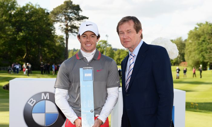 Rory McIlroy (L) poses with the trophy and European Tour Chief Executive George O'Grady following his victory at the end of day four of the BMW PGA Championship at Wentworth on May 25 in Virginia Water, England. (Ross Kinnaird/Getty Images)