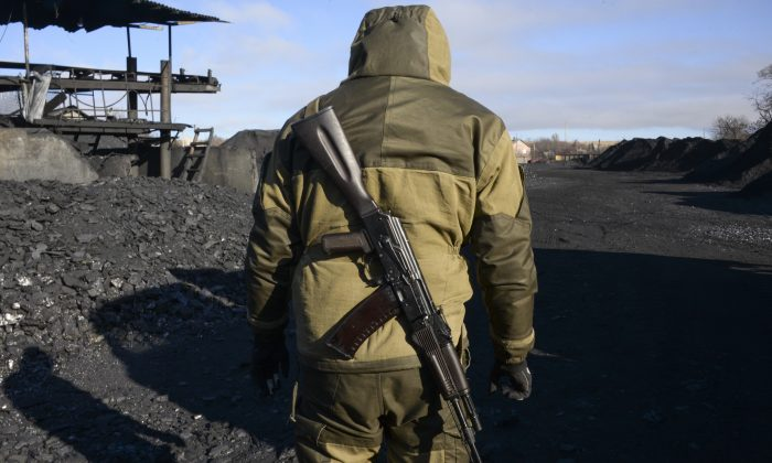 A pro-Russia rebel patrols an illegal coal mining warehouse in Torez, eastern Ukraine, on Nov. 20, 2014. As battle raged in rebellion-wracked eastern Ukraine, cargo trains piled high with coal thundered along rail tracks to keep heating and power going to households in rebel-held territory. Coal is the lifeblood of this region dominated by pro-Russian separatists—and now the source of its first corruption scandal. (AP Photo/Mstyslav Chernov)