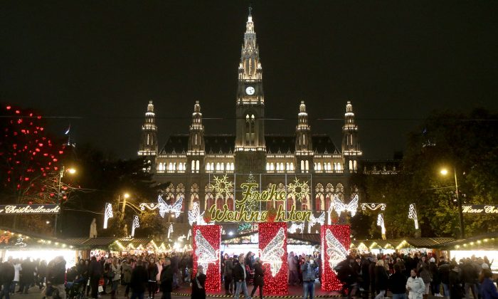 "In this picture taken Sunday, Nov. 16, 2014 visitors crowed the Christmas market in front of the neo-Gothic City hall in Vienna, Austria. Nothing will put you more in the mood for the festive season than the Christmas markets big and small dotting the city. Choices range from the more than 150 wooden huts set up in front of the City hall, to markets often no bigger than a few booths. Among the hundreds of goods on offer are tree lights, candles, ornaments and musical Christmas toys. Letters read ""Merry Christmas"". (AP Photo/Ronald Zak)"