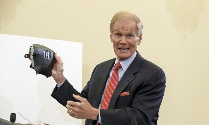 Senate Commerce Committee member Sen. Bill Nelson (D-Fla.) displays the parts and function of a defective airbag made by Takata of Japan that has been linked to multiple deaths and injuries in cars driven in the US, Thursday, Nov. 20, 2014, during the committee's hearing on Capitol Hill in Washington. (AP Photo/J. Scott Applewhite)
