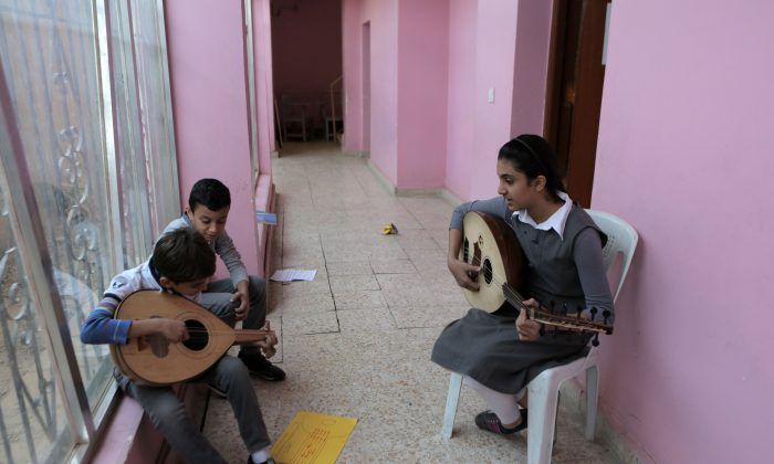 In this Nov. 12, 2014, photo, students practice music in the hallway because of limited classrooms at the Baghdad School of Music and Ballet in Monsur district in Baghdad. The school was looted days after Saddam Hussein's ouster. Later it was partially burned during a rampage by disgruntled Saddam-era officers. (AP Photo/Khalid Mohammed)