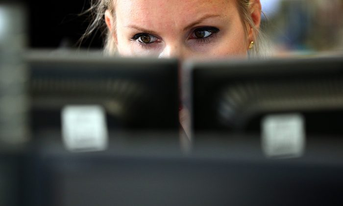 An employee views trading screens at the offices of Panmure Gordon and Co on Oct. 20, 2014 in London, England. (Carl Court/Getty Images)