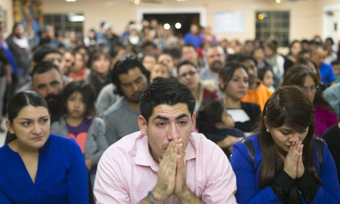 (L-R) Viridiana Carrizales of San Antonio, Texas; Jose Patino, of Phoenix; and his girlfriend Reyna Montoya of Mesa react during a watch party for President Obama's speech on immigration at the Puente offices in Phoenix on Nov. 20, 2014. (David Wallace/The Republic via AP)