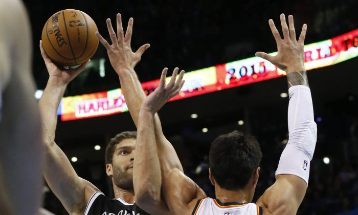 Brooklyn Nets' Brook Lopez (11) shoots as Oklahoma City Thunder's Steven Adams (12) defends during the first quarter of an NBA basketball game in Oklahoma City, Friday, Nov. 21, 2014. (AP Photo/Sue Ogrocki)